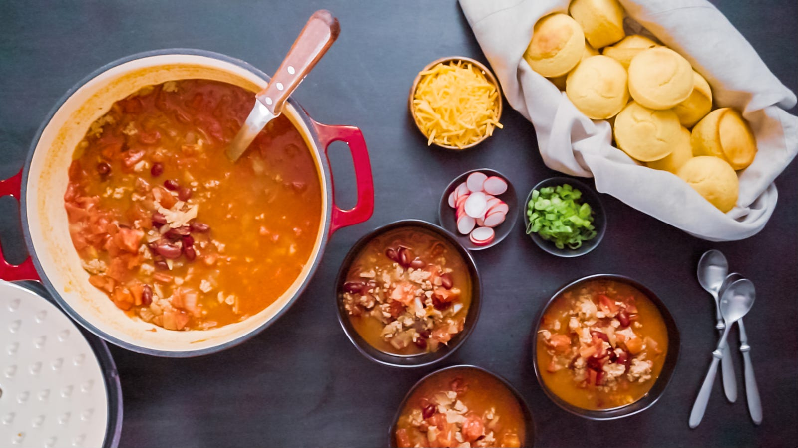 An enameled Dutch oven filled with a hearty chili with rolls and all the chili fixings ont the side.