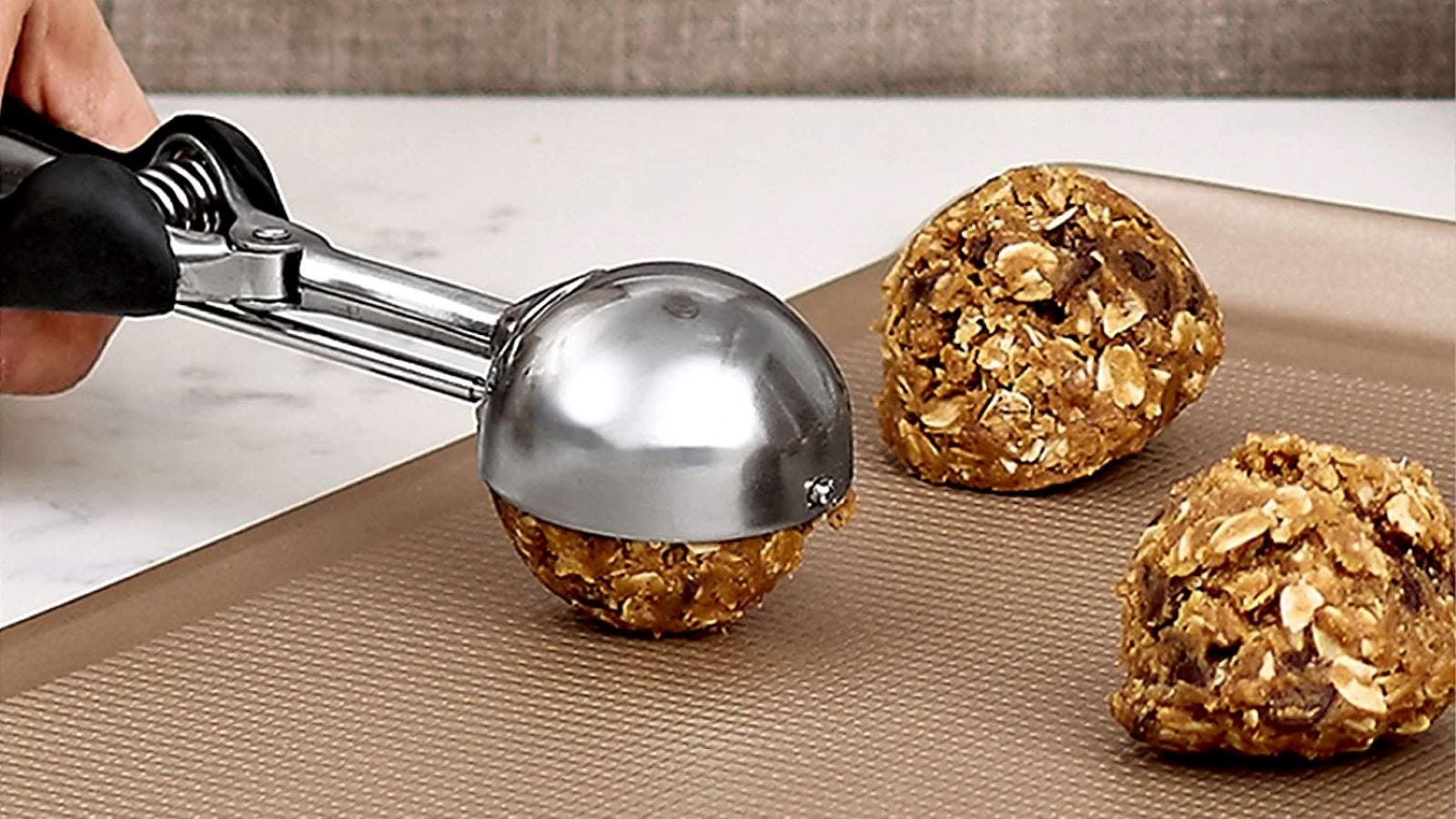 Someone scooping cookie dough onto a cookie sheet with the OXO Good Grips Cookie Scoop.