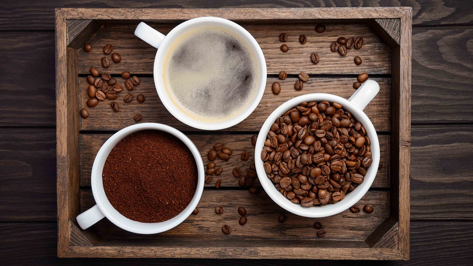 Whole coffee beans, ground coffee and a cup of hot brewed coffee placed on a rustic wooden tray with various beans spread on the tray.