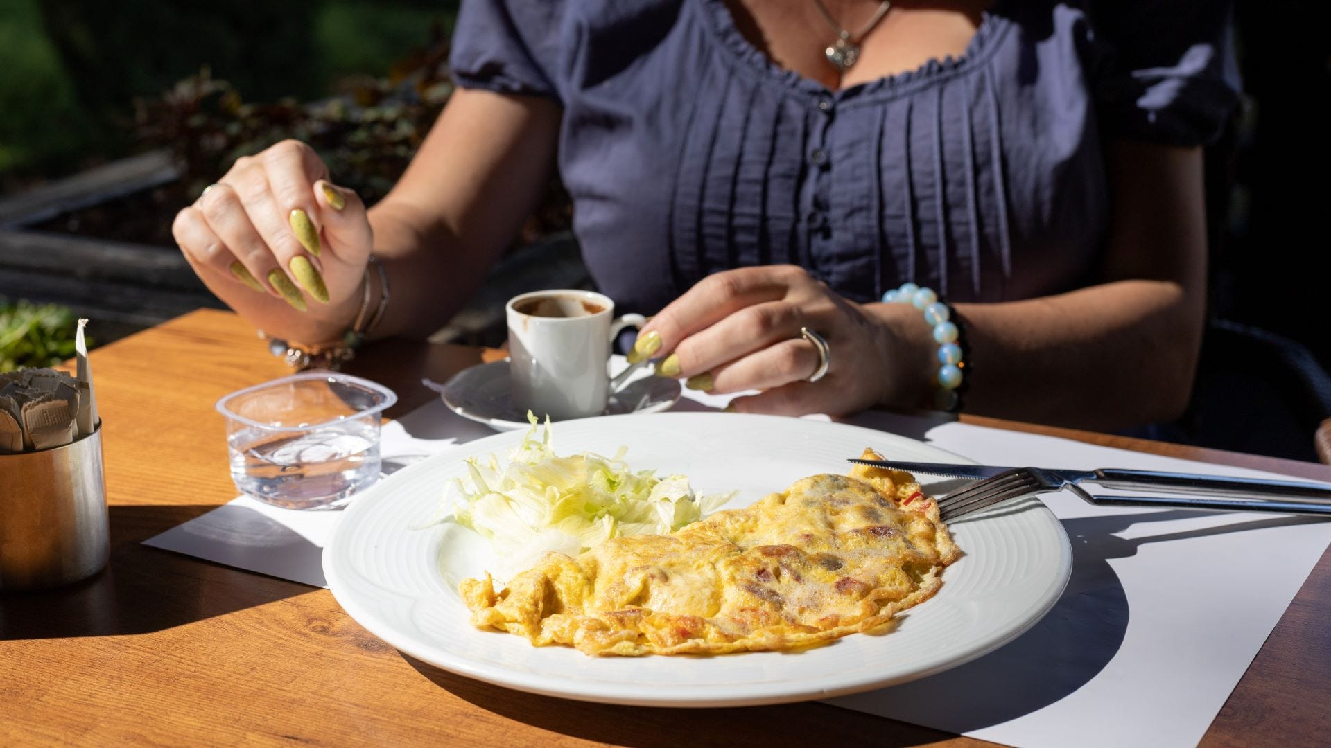 A woman having an omelet and coffee at an outdoor cafe.