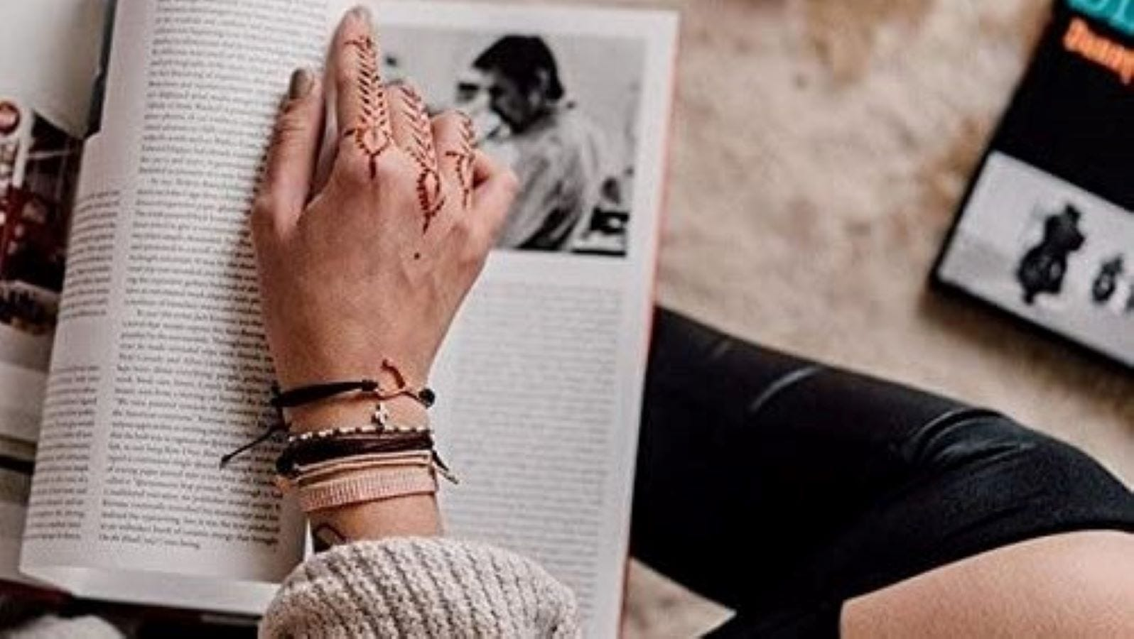 A woman reading a book and wearing a Puira Vida bracelet.