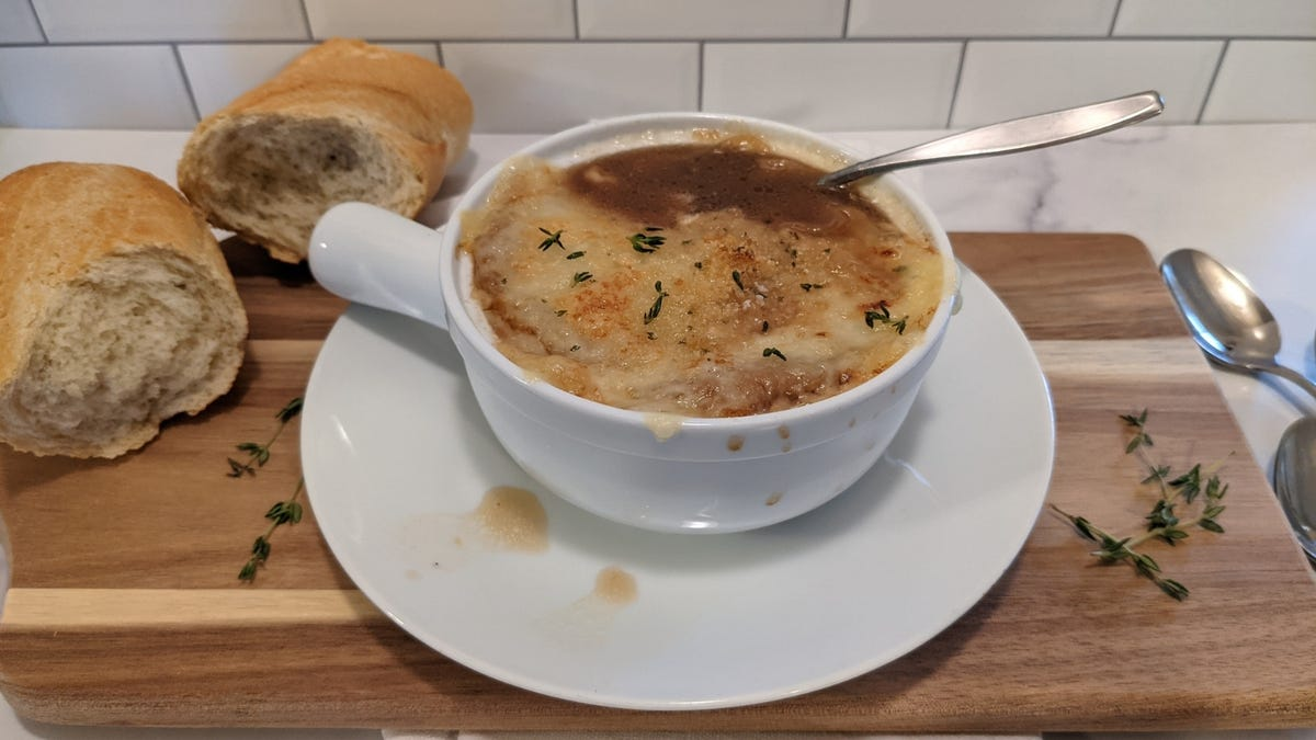 A bowl of hot french onion soup garnished with fresh thyme with two pieces of bread next to the bowl.