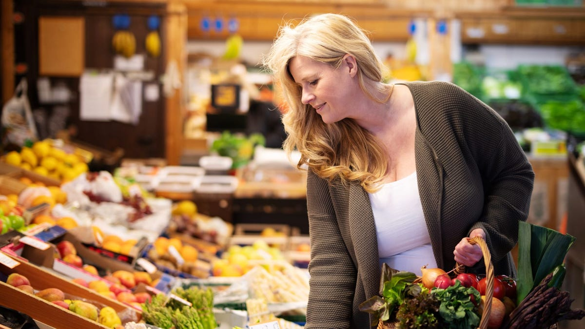 A woman shopping for produce at a grocery store.
