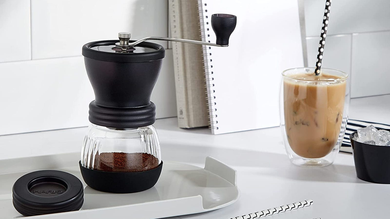 An image of the Hario ceramic mill placed over a plastic try with an iced coffee dirnk on the side.