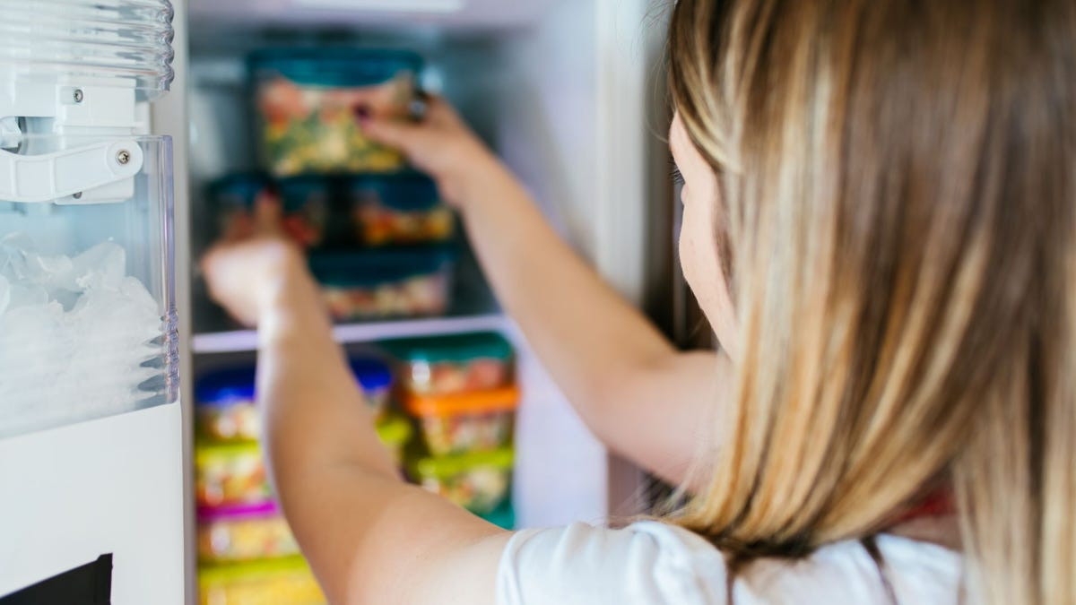 Woman placing a container of mixed vegetables in a freezer.
