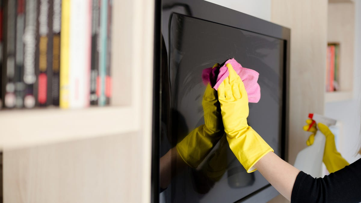 A person wearing gloves wipes down a flat screen television.