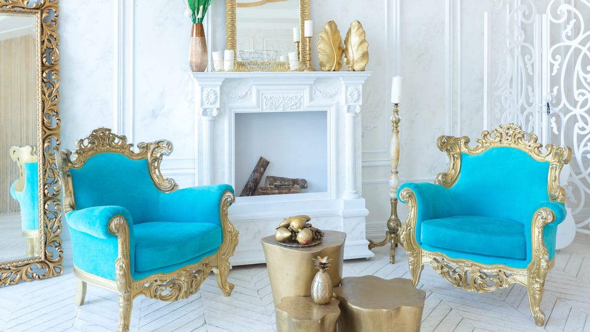 Two bright blue chairs with gold embellishments are in front of a fireplace.