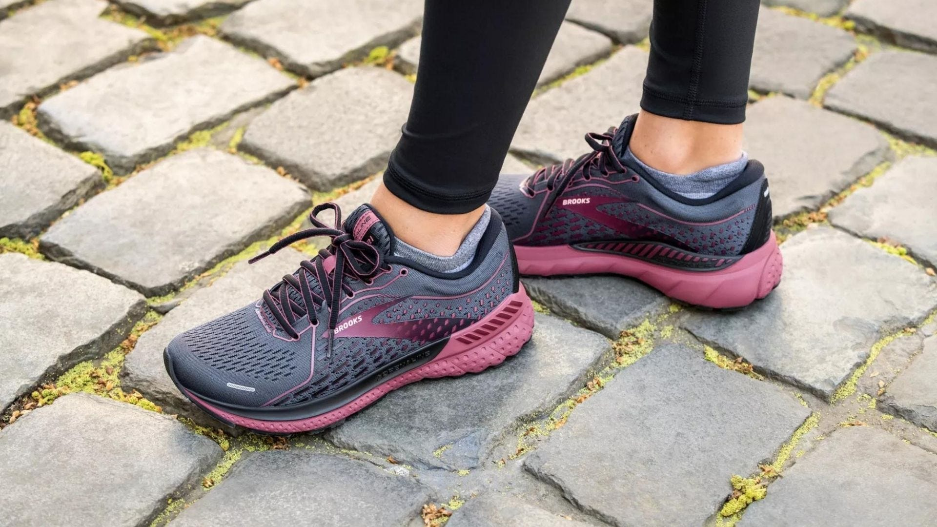 Someone wears a pair of black and pink running shoes