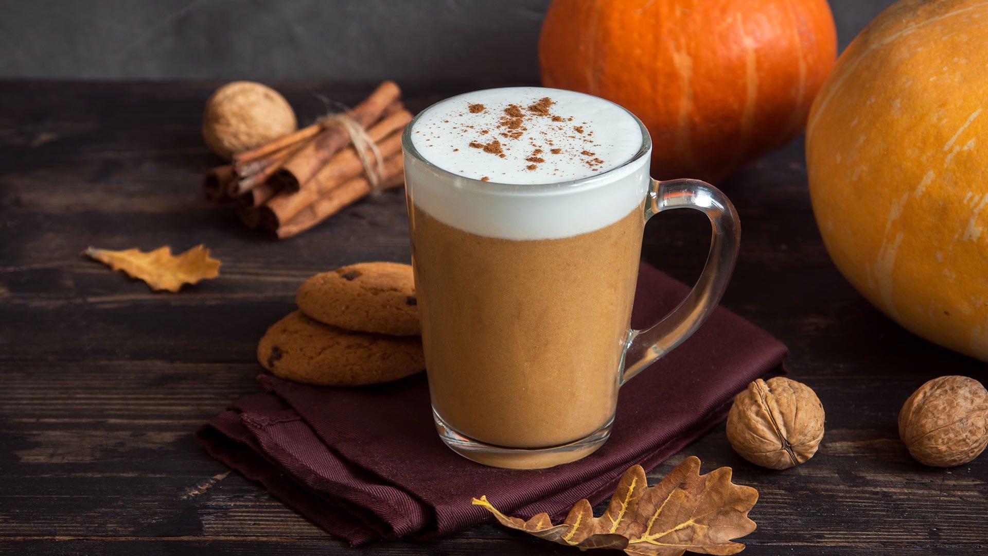 Uma bebida Pumpkin Spice Latte sobre uma mesa com biscoitos, paus de canela e abóboras.