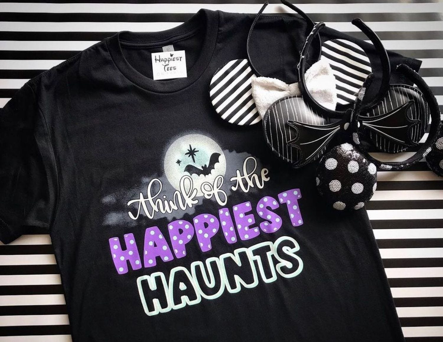 """A black T-shirt with writing reading """"Think of the happiest haunts"""""""