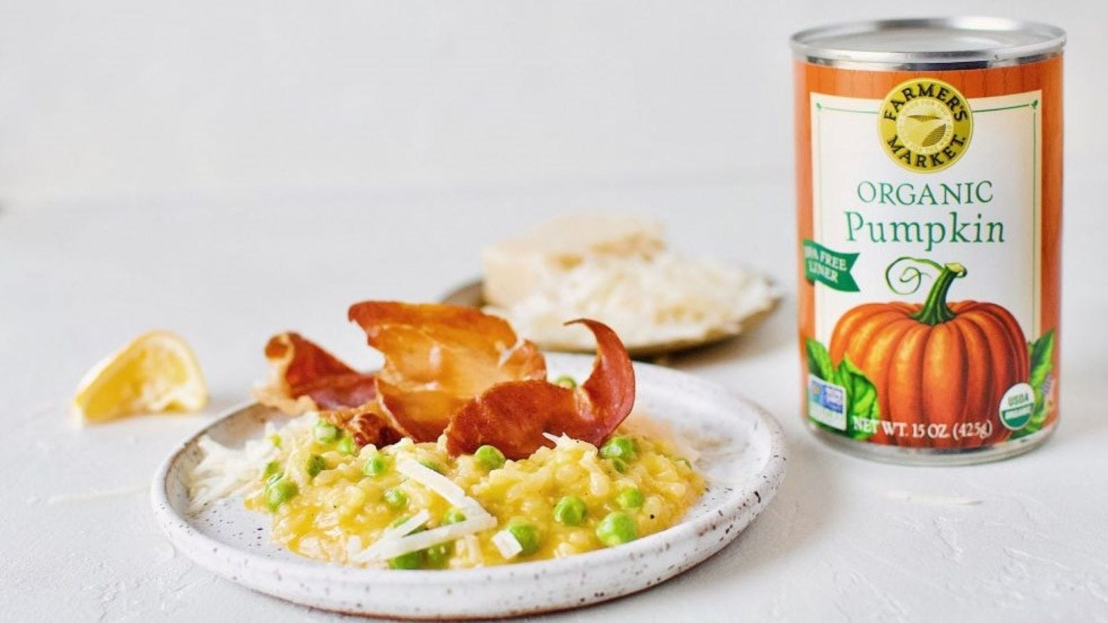 A can of Farmer's Market Organic Pumpkin next to a plate of risotto.