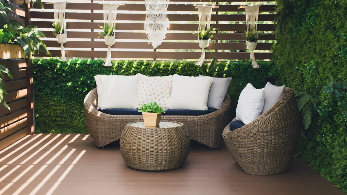 Couches are surrounded by greenery covered walls.