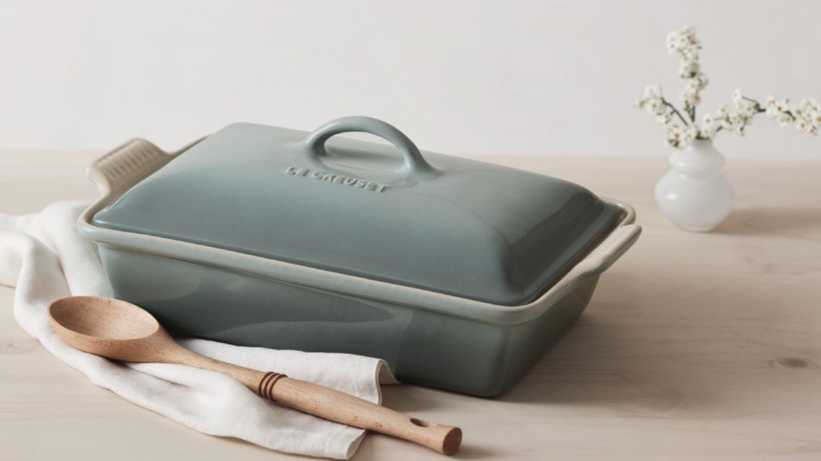 Le Creuset Stoneware Covered Rectangular Casserole Dish and a wooden spoon on a table.