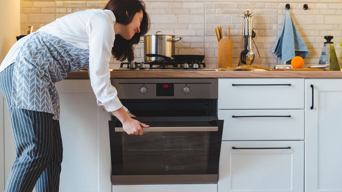 A woman opens an oven.