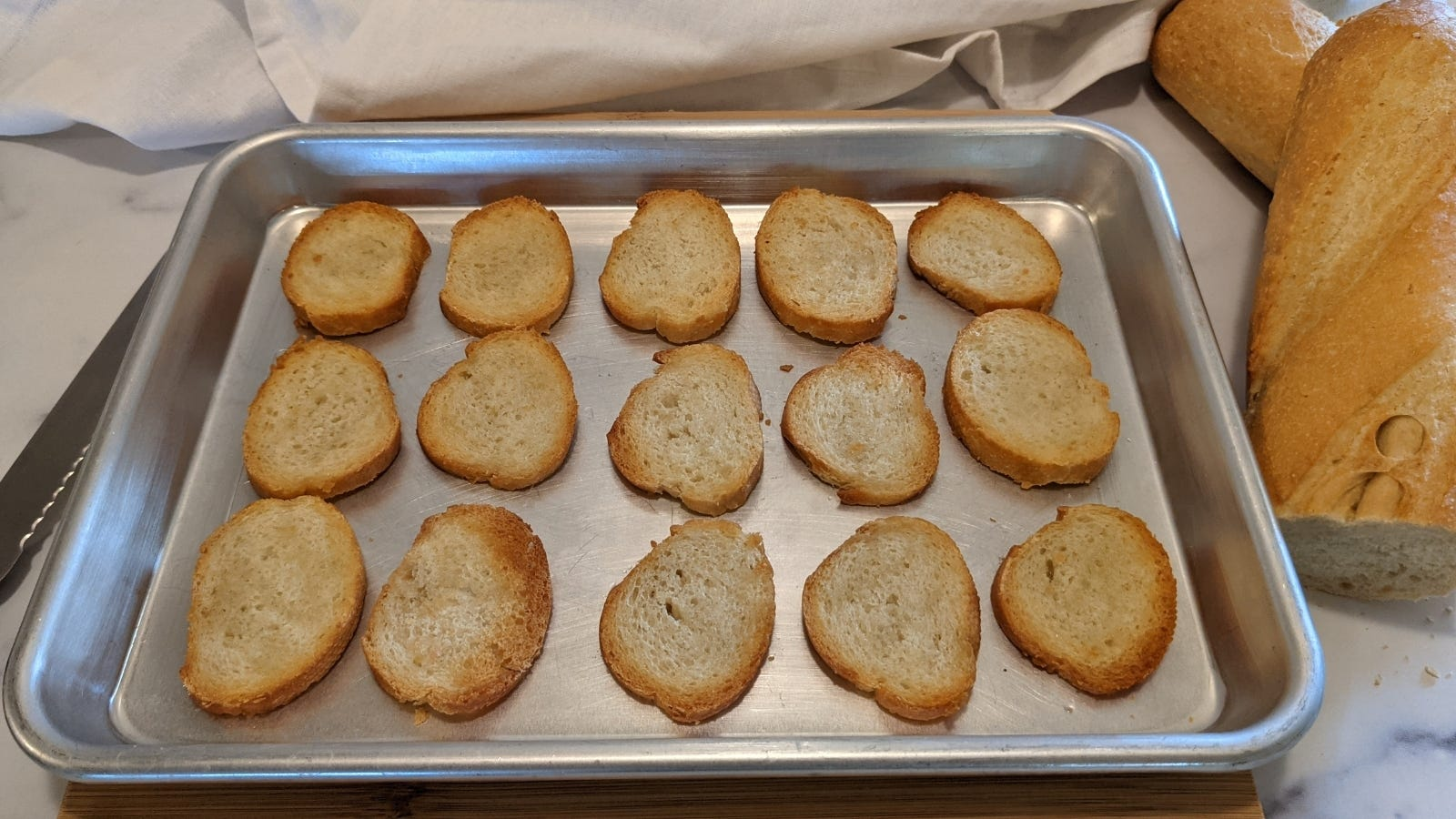 Multiple slices of French baguette placed on a sheet pan, freshly toasted in the oven.
