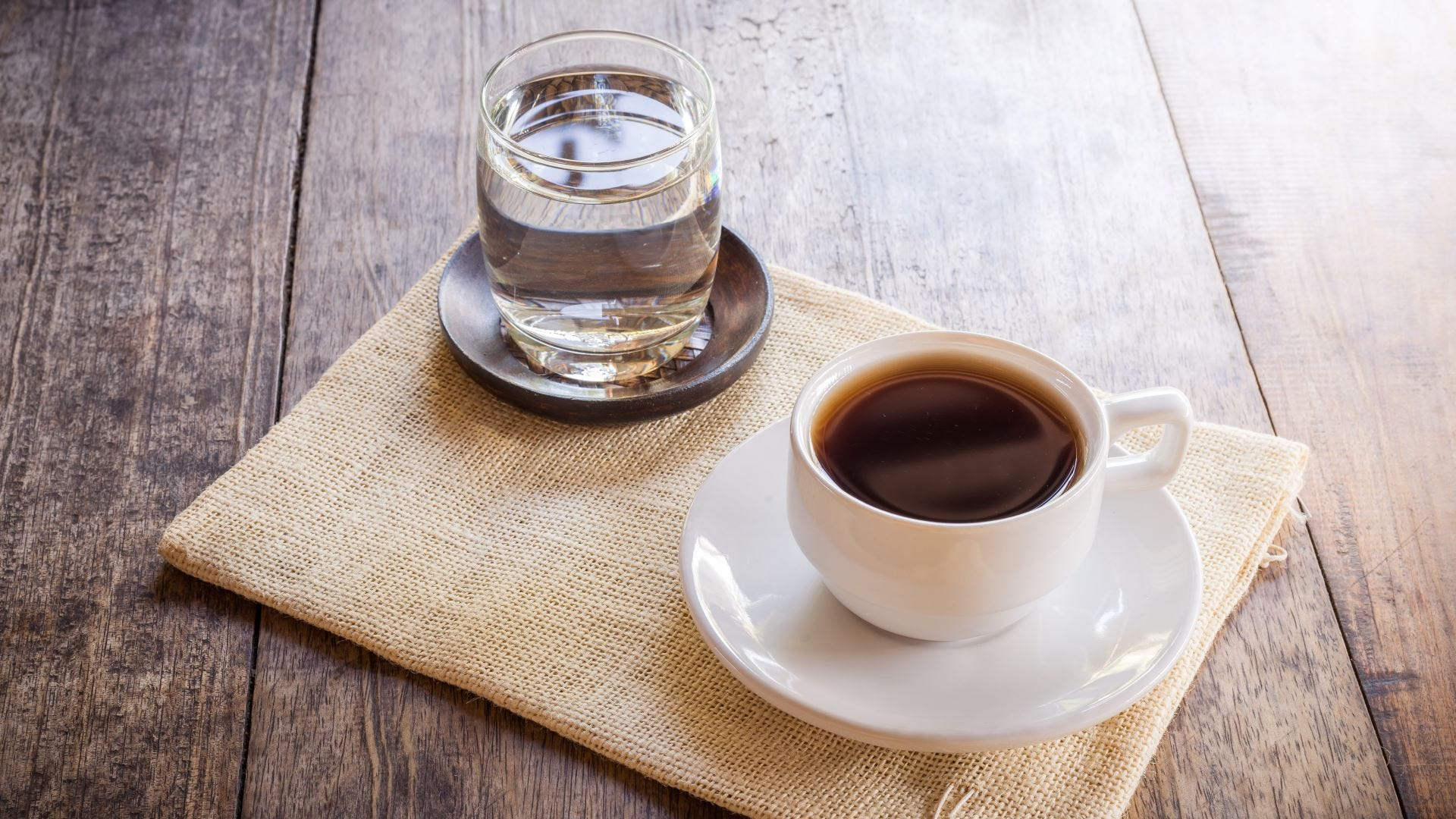 A glass of water sititng next to a mug of coffee.