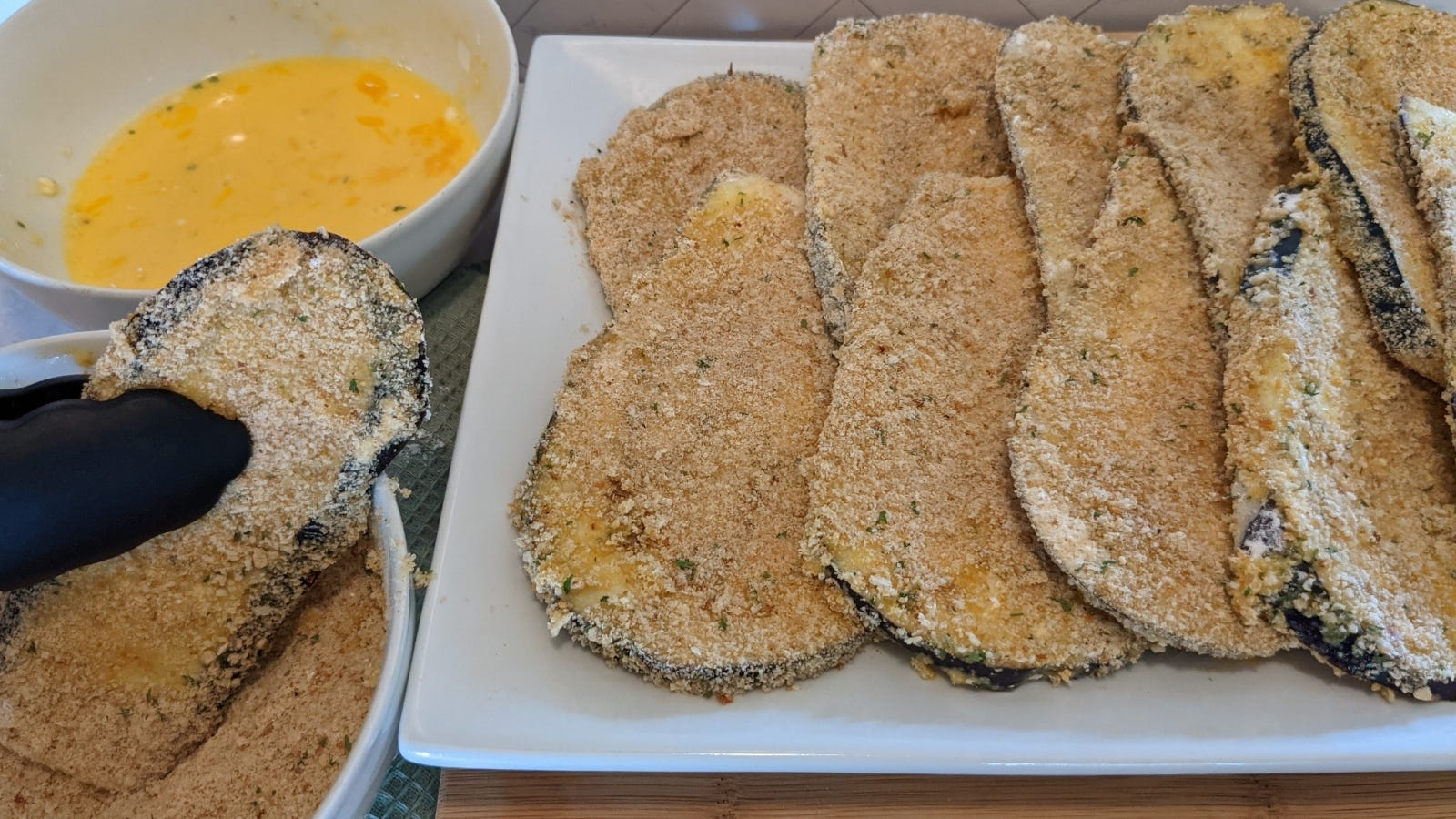Transfering a coated slice of eggplant, covered in breadcrumbs, ready to go into the skillet.