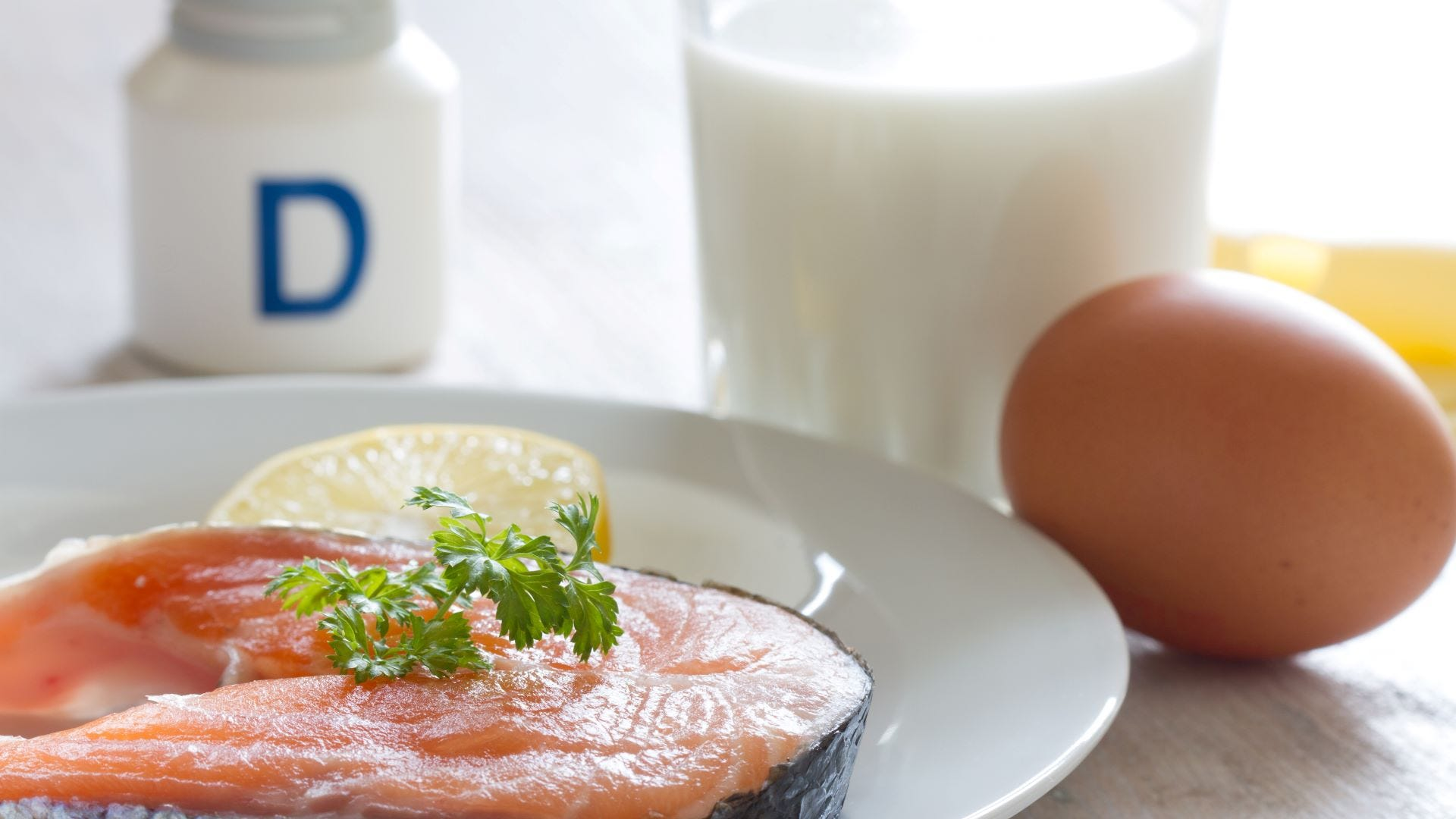 Salmon on a plate next to a glass of milk, an egg, and a bottle of vitamin D.