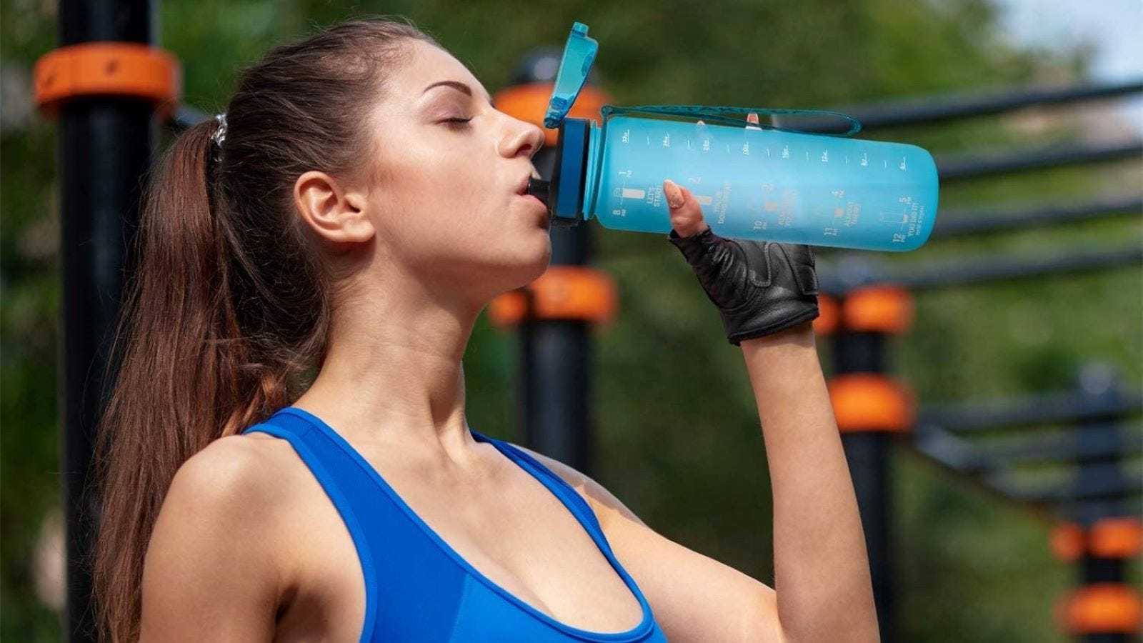 A woman drinking out of a blue Cactaki Water Bottle.
