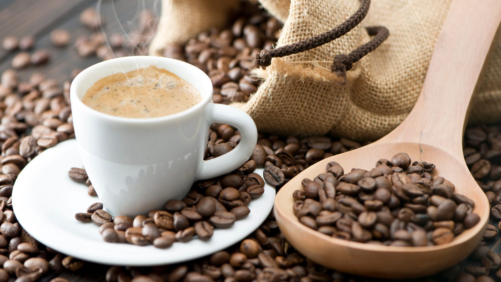 A cup of espresso next to coffee beans spilling out of a bag with a wooden spoon that has plenty of beans.