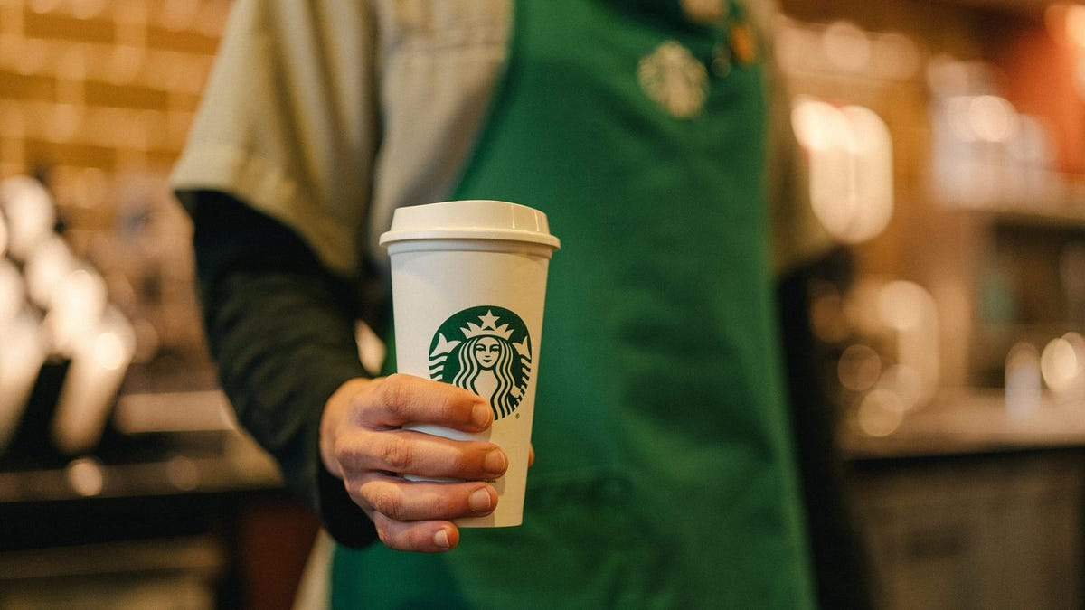 A Starbucks barista holds a coffee cup.