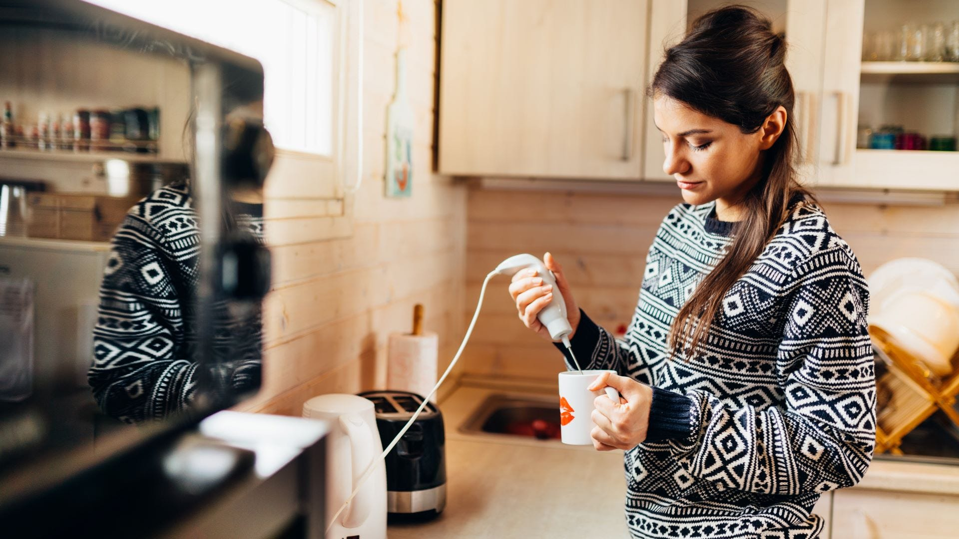 A woman using a milk frother making a mug of whipped coffee.