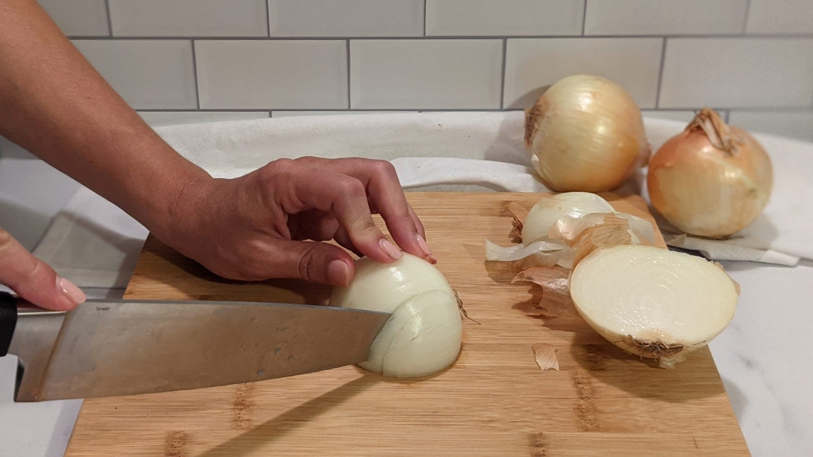 Slicing an onion vertically multiple times, with onions and onion peels on the side.