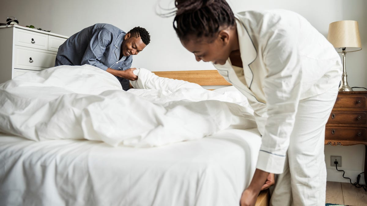 A couple makes the bed.