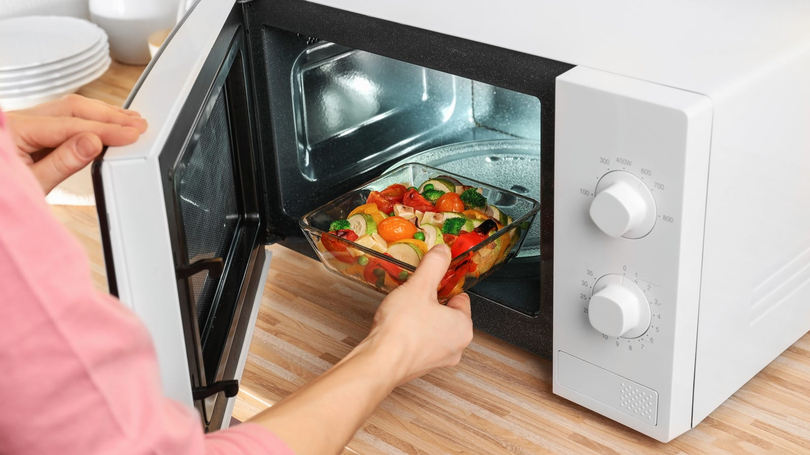 A person placing food in the microwave, to try and reheat and kill the bacteria groth for safe eating.