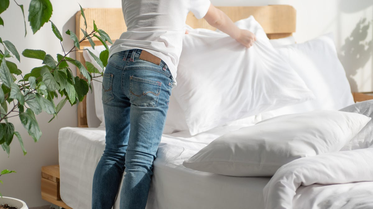 A woman puts sheets on a bed.