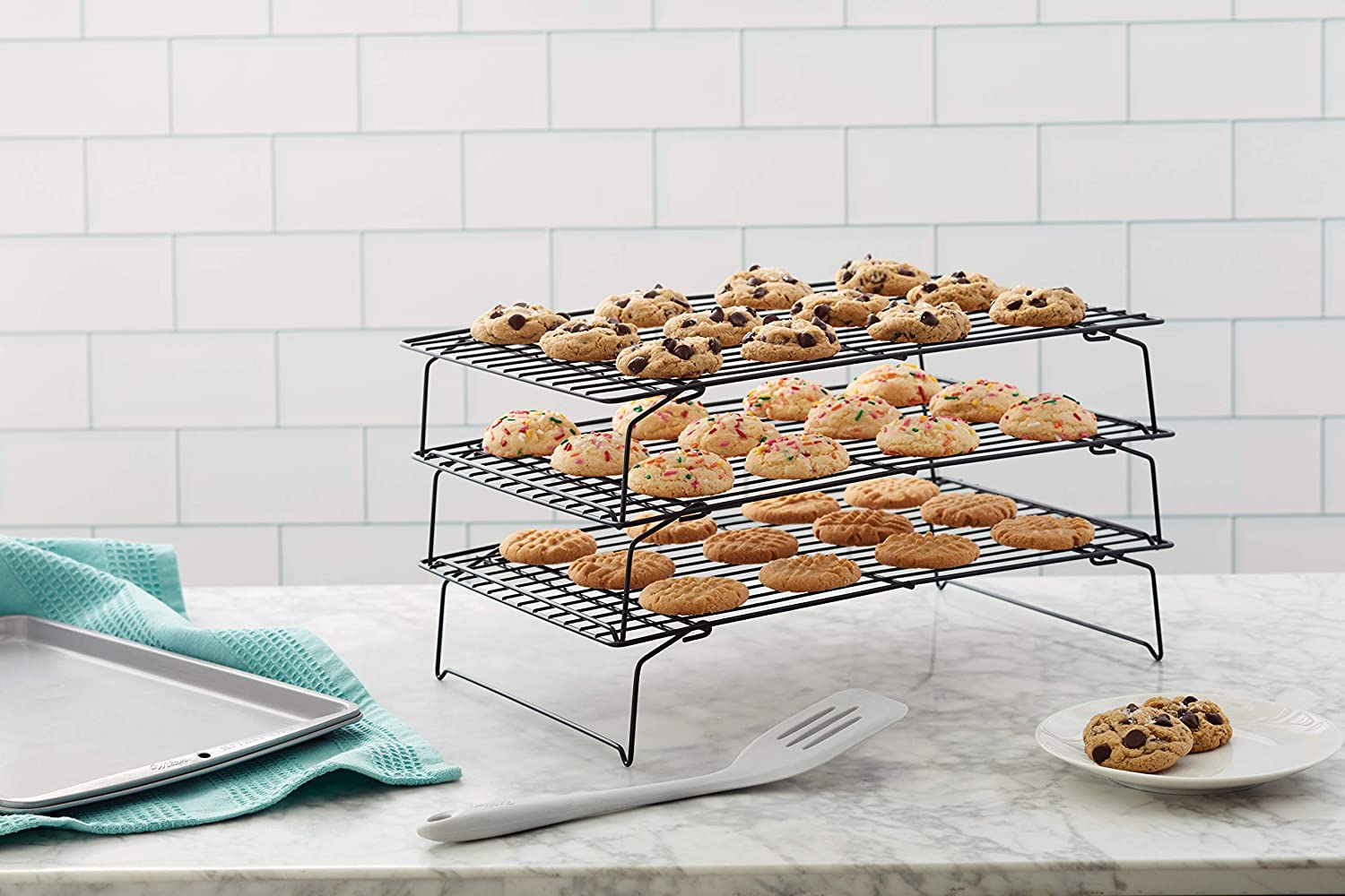 A three-tier cooling rack with cookies, sitting on a marble countertop