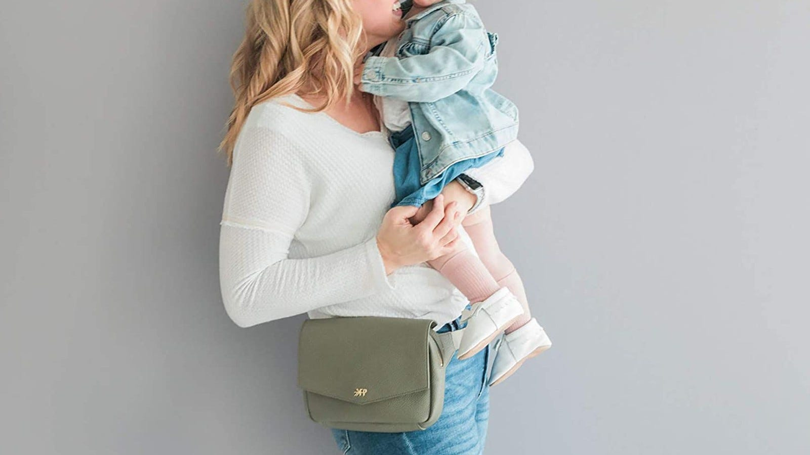 mom holding toddler and wearing a green Freshly Picked fanny pack
