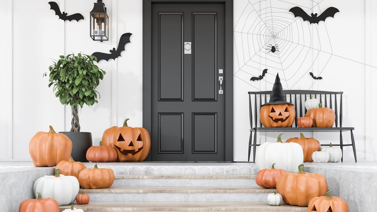 Pumpkins, bats, and cobwebs decorate a front porch.