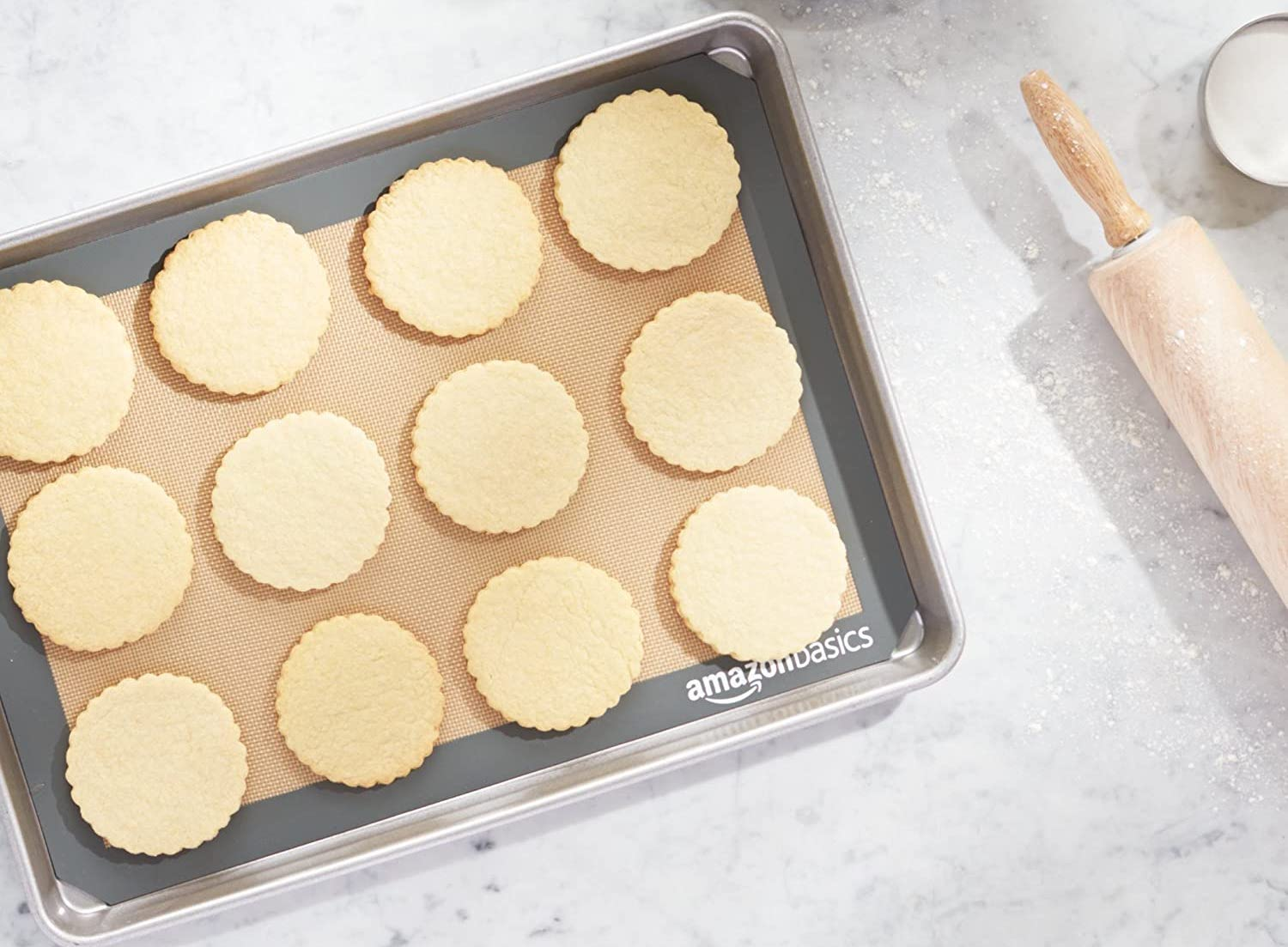 Cookies sitting on a silicone mat on a cookie sheet, with a rolling pin nearby