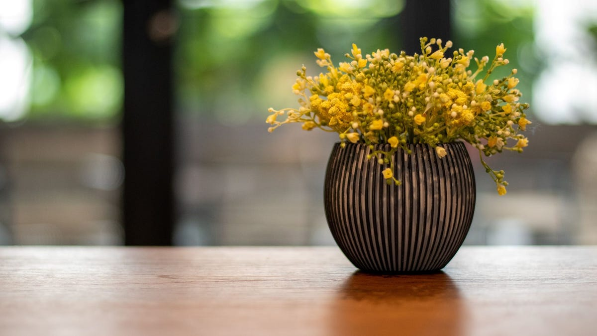 A flower vase sitting on a table according to the rule of thirds.