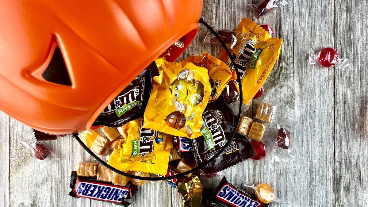 Candy spills from a plastic pumpkin.