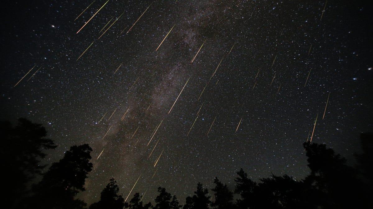 Meteors shoot through a night sky.