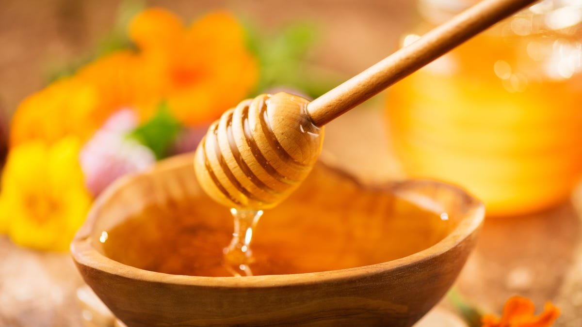 A honey dipper drizzles honey into a bowl.