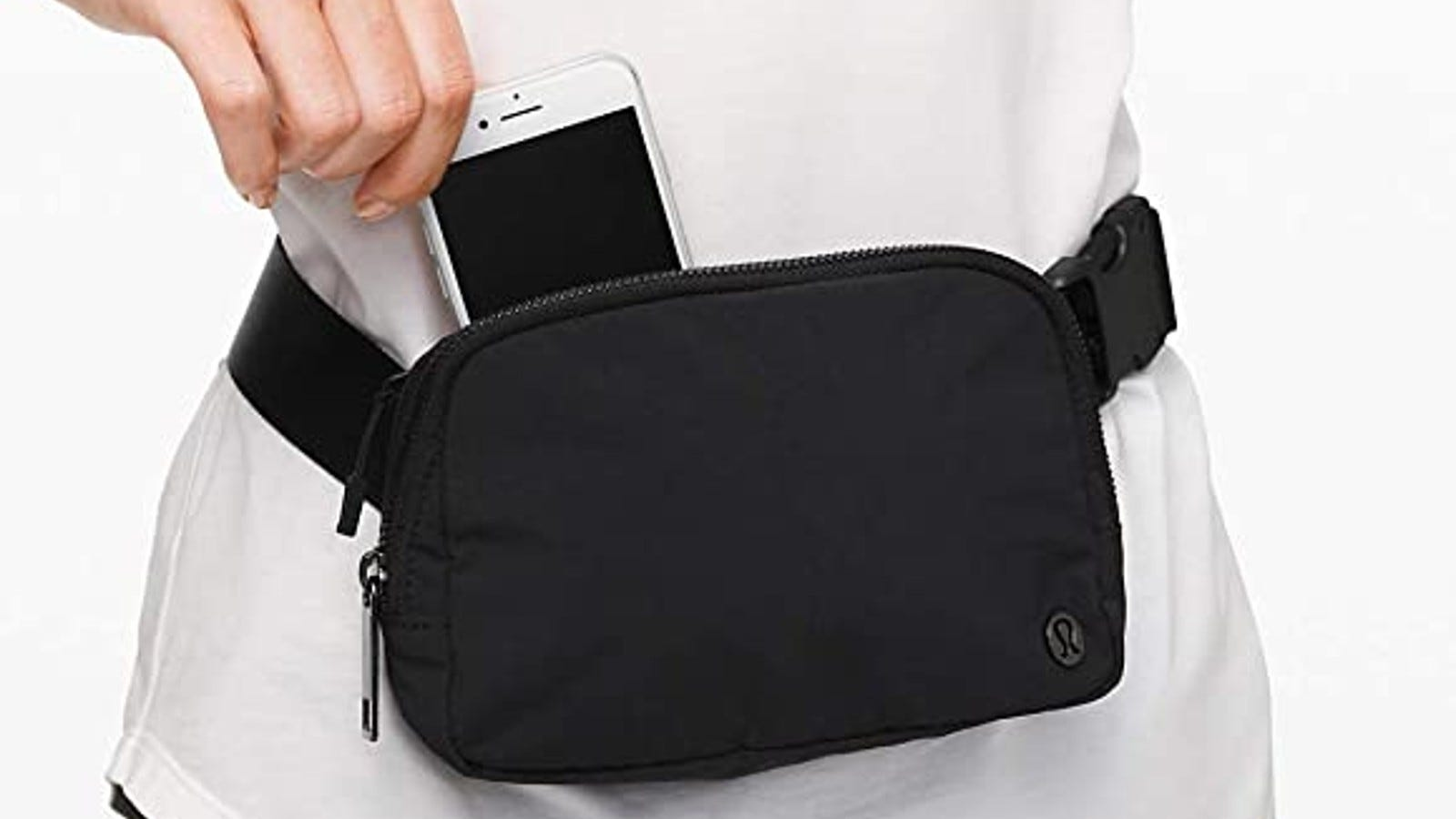 black fanny pack on woman's waist while she pulls her iPhone out
