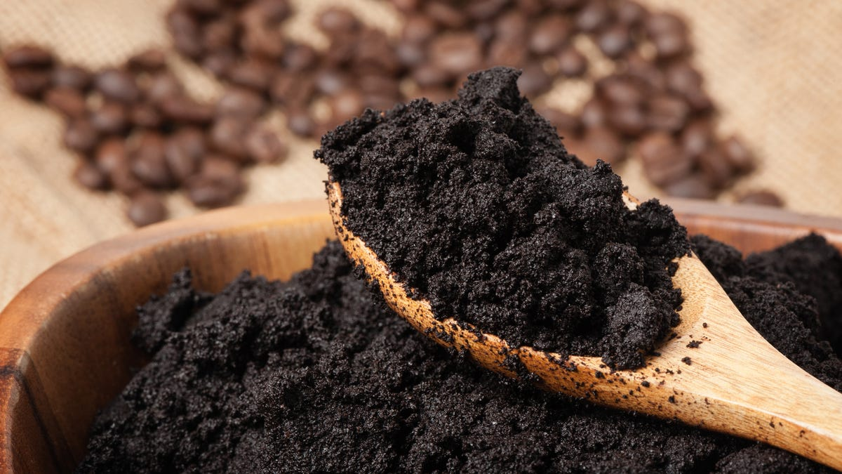 A person scoops up coffee grounds with a spoon.