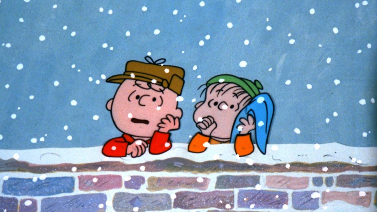 Charlie Brown and Linus are propped on a brick wall.