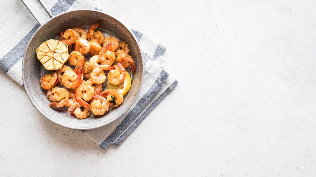 Shrimp sits in a saute pan.