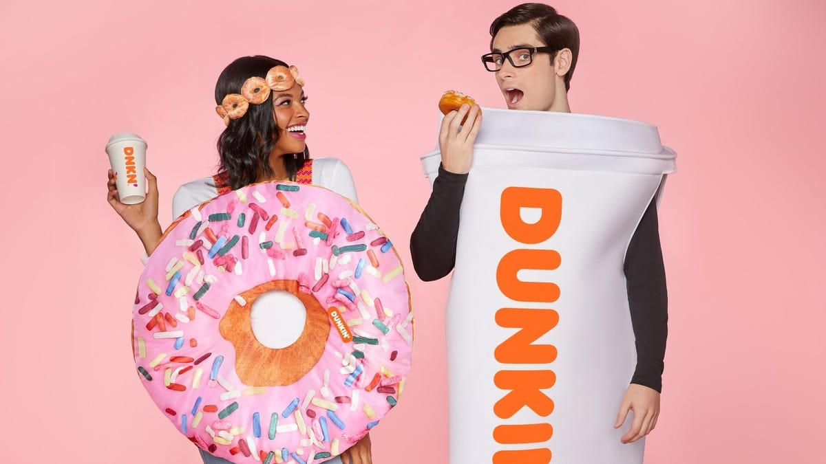 A woman in a strawberry donut costume and a man in a Dunkin' Donuts to-go coffee cup costume from Spirit Halloween.
