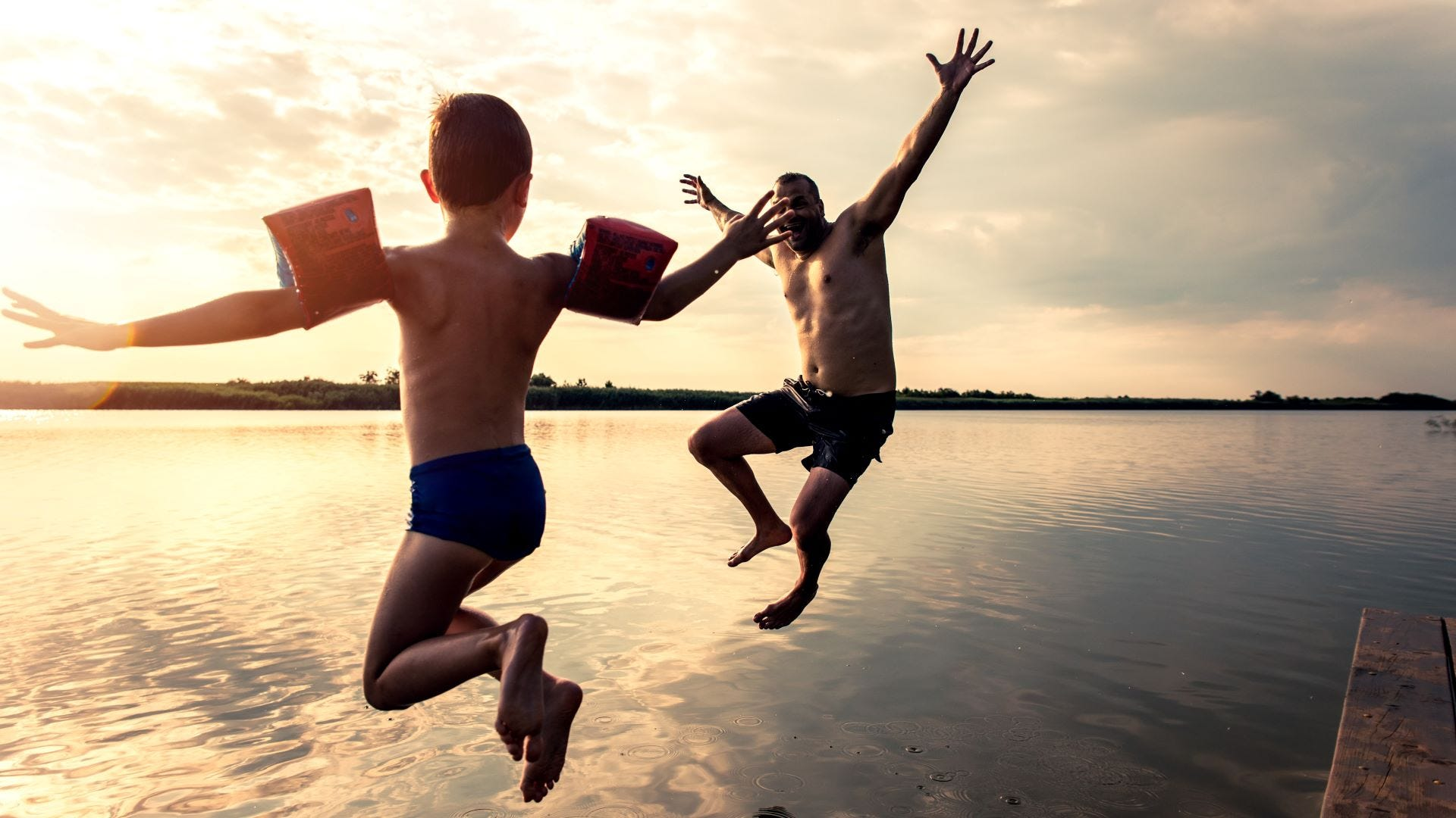 A father and son jumping in a lake.