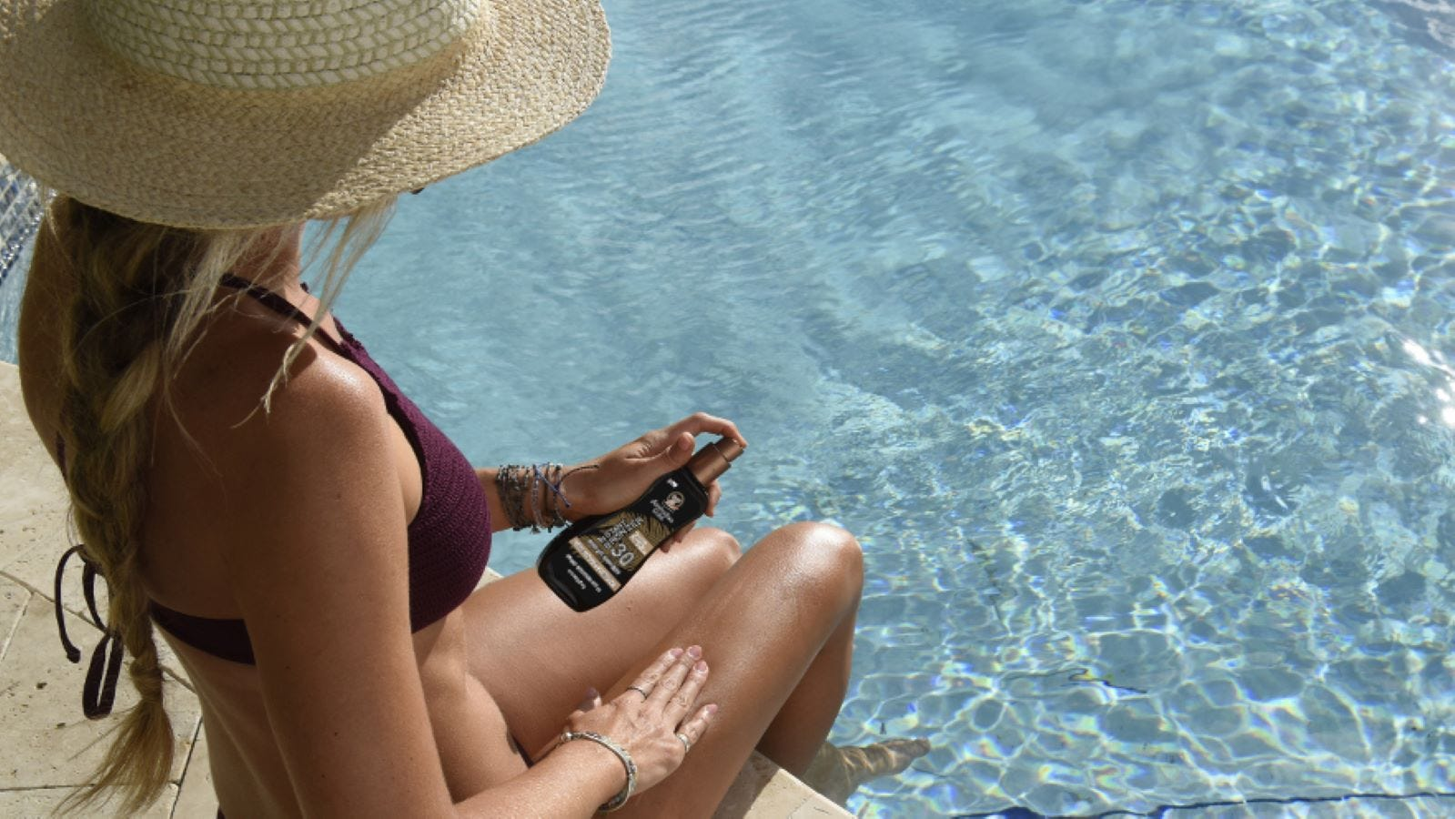 A woman by a pool applying Australian Gold Instant Bronzer 30 SPF.