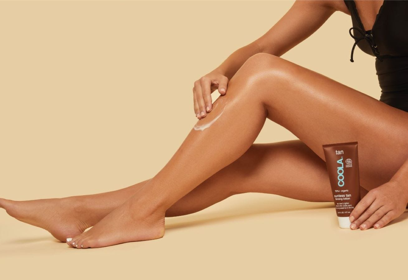A woman applying Coola sunless tanning firming lotion to her legs.