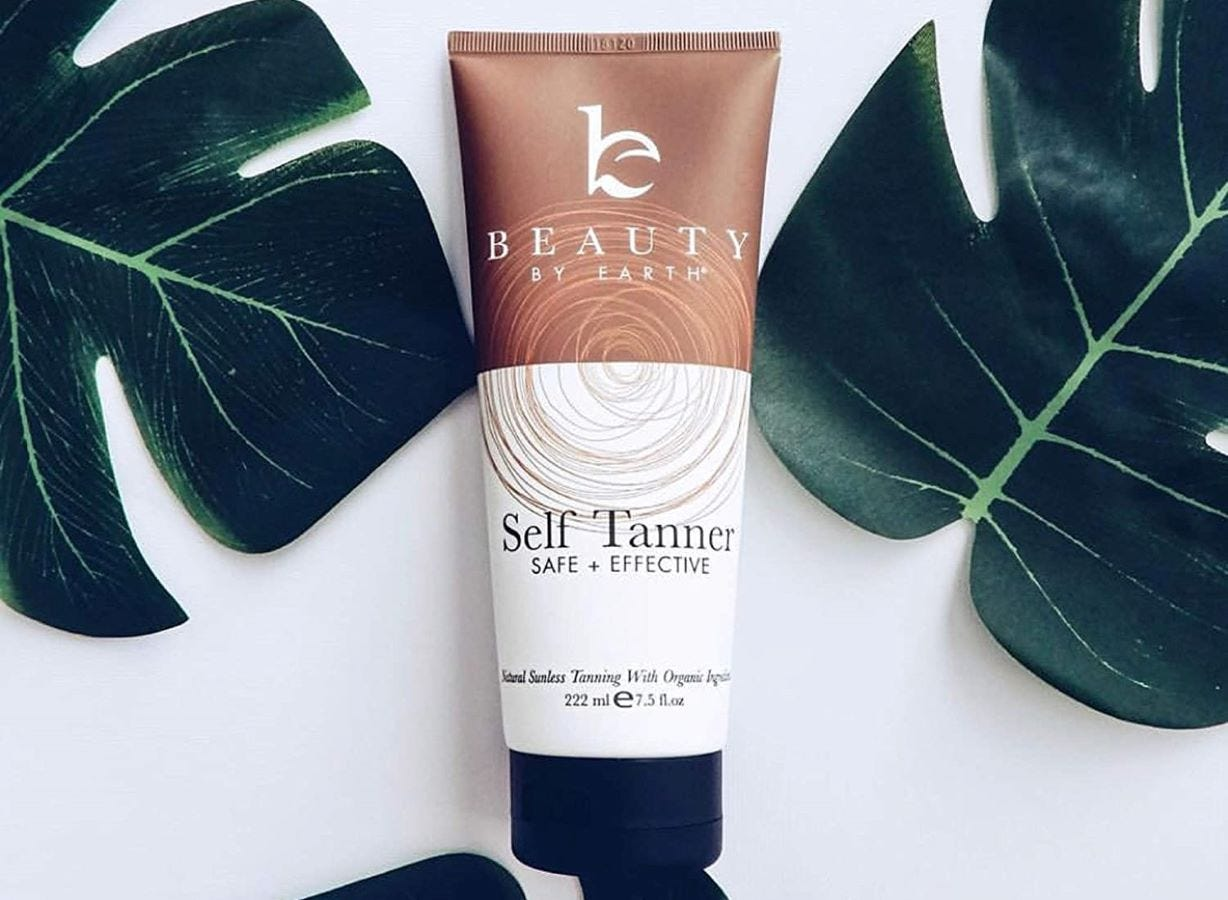 A tube of Beauty By Earth Self tanner surrounded by green leaves.