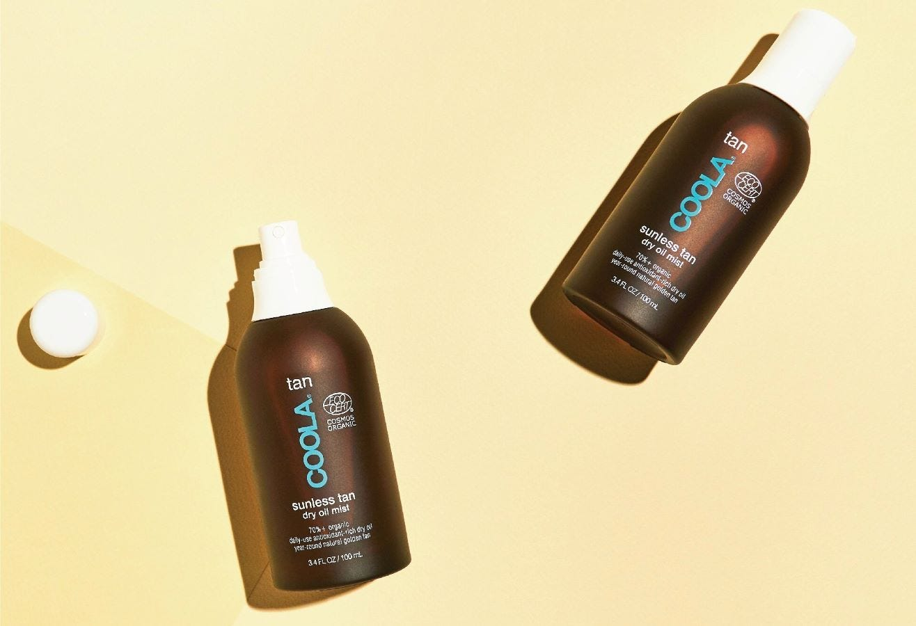 Two bottles of COOLA Sunless Tan Dry Oil Mist.