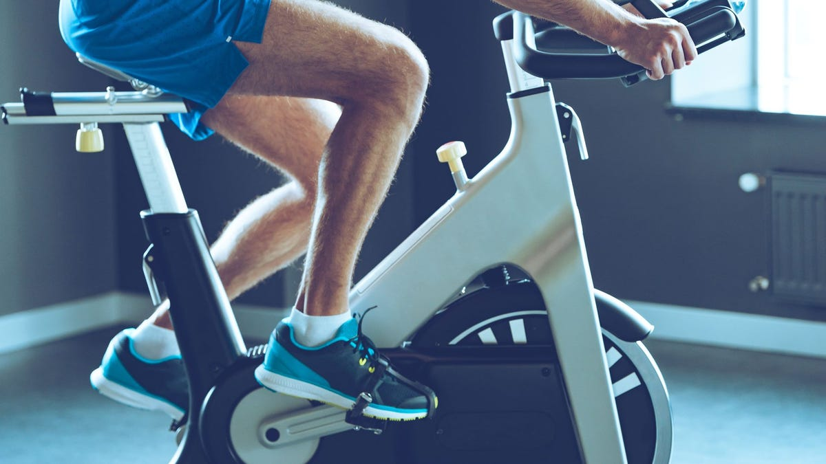 A man cycling indoors on a stationary bike.