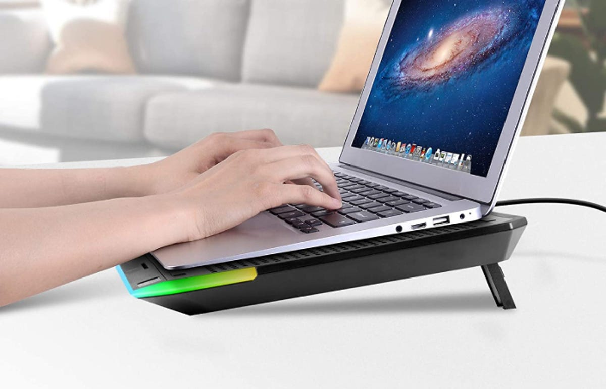 hands typing on a laptop that's resting on a cooling pad